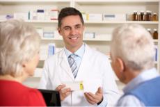 Pharmacist talking to elderly couple